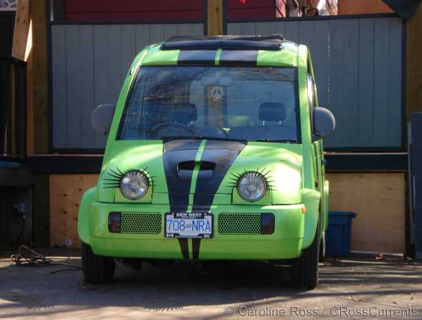 Photo of a lime green Nissan S-Cargo van with eyelashes attached around the headlights.